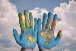 blog graphic of the world painted on two adult hands