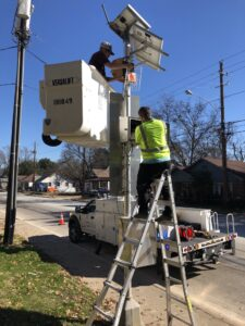 crew installing air monitor on a pole